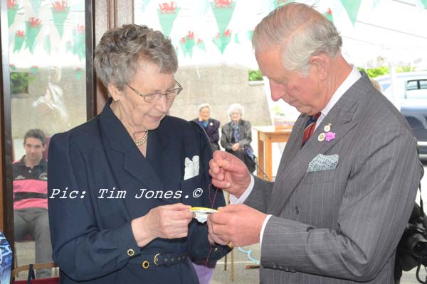 HRH The Prince of Wales placing the final stitch in an embroidered tablecloth by Llanddewi Brefi WI